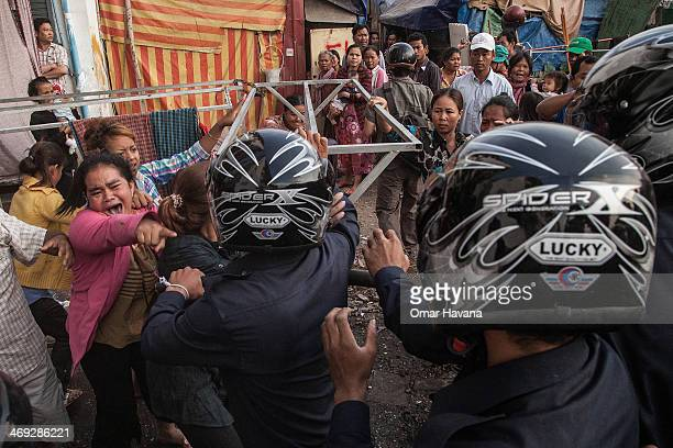 A woman shouts slogans to municipal police forces during clashes in the Borei Keila community on February 14 2014 in Phnom Penh Cambodia A building...