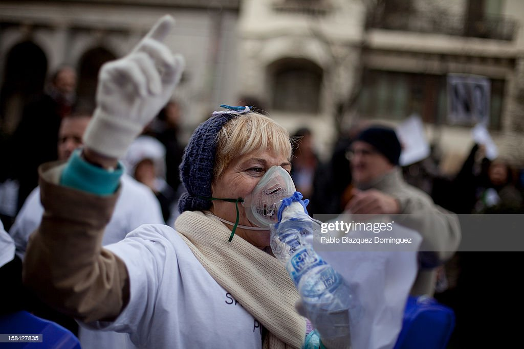 A woman shouts slogans while wearing a breathing mask amid other health workers during a demonstration against cuts on public health care and the privatization of medical centers and hospitals on December 16, 2012 in Madrid, Spain. In Madrid, doctors have already staged 11 days of strikes and all health workers unions are calling for a third 48 hour strike on December 19 and December 20. Around 4,000 operations have been suspended in Madrid since the medical strikes started.