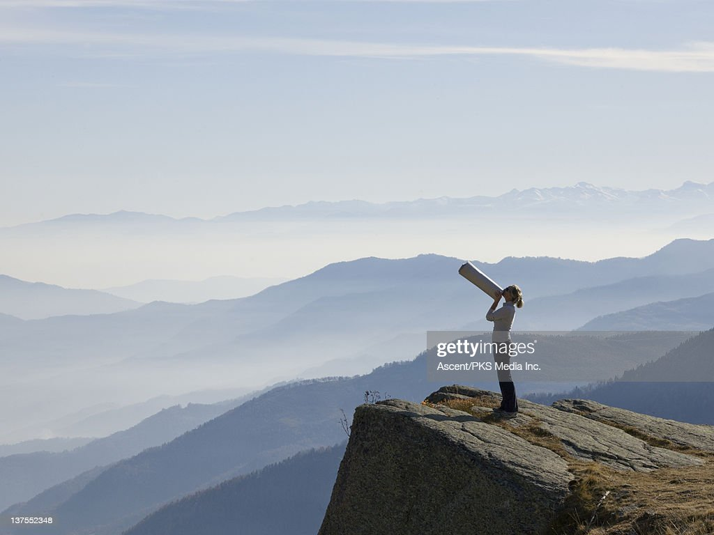 Woman shouts through megaphone, above mtns : Stock Photo