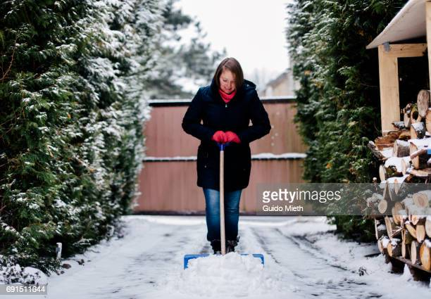 Woman shoveling snow on the driveway.