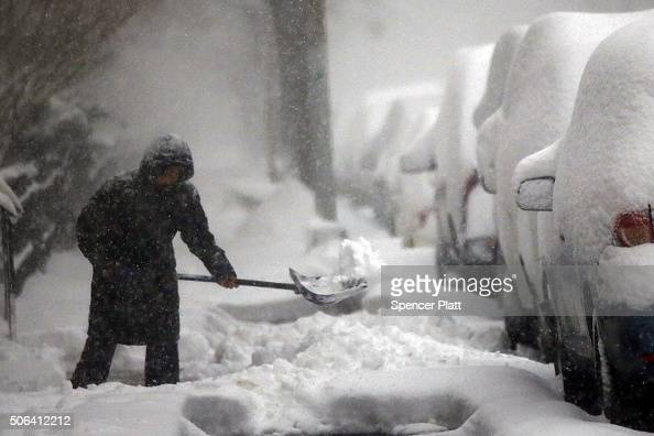 A woman shovels a sidewalk in blizzardlike conditions on January 23 2016 in the Brooklyn borough of New York City The Northeast and parts of the...