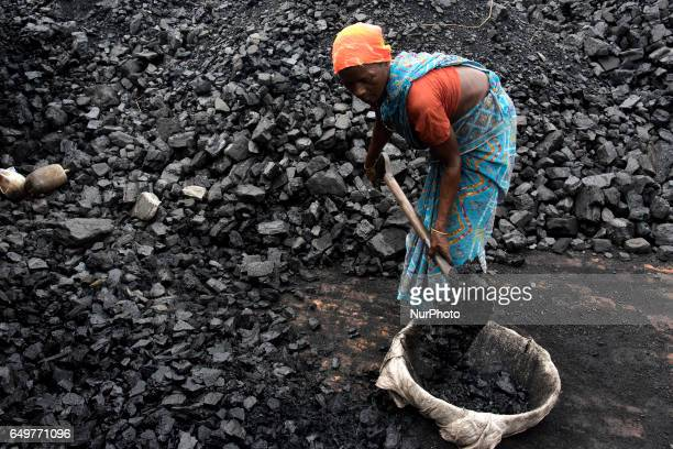 Woman shovels coal in Kamduni brick kiln Kamduni West Bengal India 080317 The brick kilns of Bengal employ a large number of laborers from distant...