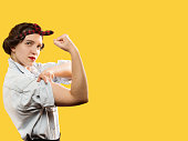 strong woman show her biceps on yellow background with copy space