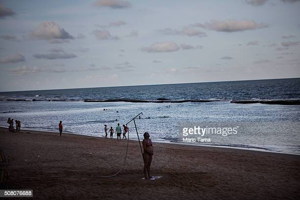 A woman showers on the beach on February 2 2016 in Recife Pernambuco state Brazil In the last four months authorities have recorded thousands of...