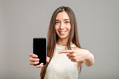 Portrait of a young amazed woman showing blank smartphone screen over gray background