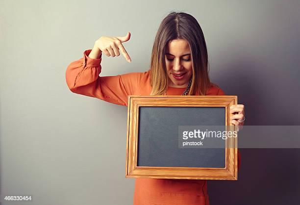 Donna mostrando scheda davanti al muro.