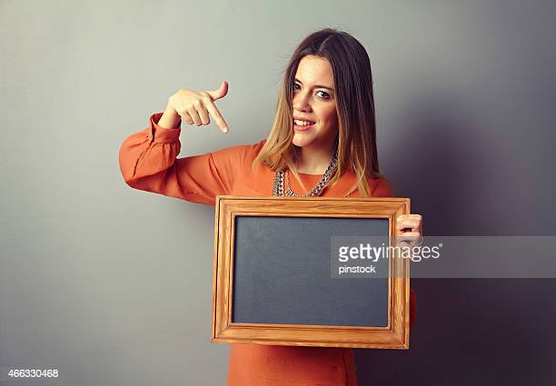 Woman showing board in front of the wall.