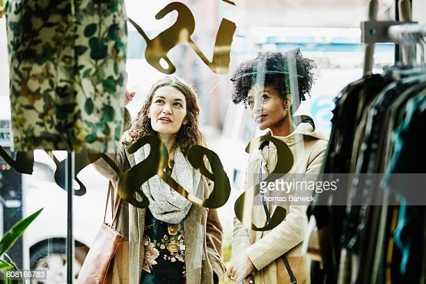 Woman showing friend dress in window of boutique