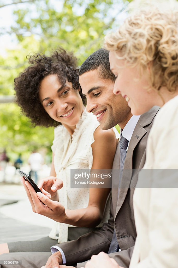 Woman showing her cell phone to friends : Foto de stock