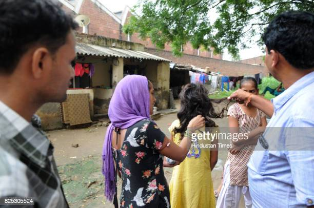 Woman showing her daughter's braids which were chopped by unknown person near Ravi Nagar on August 1 2017 in Gurgaon India According to media reports...