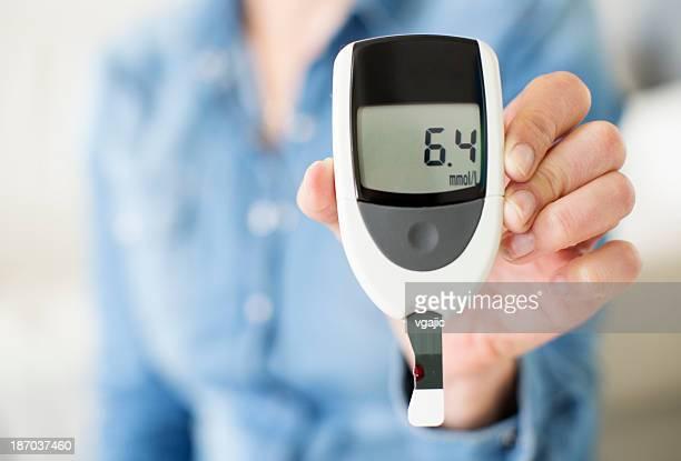 Mujer mostrando su nivel de glucosa de prueba.