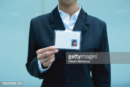 Woman showing identity card, mid section
