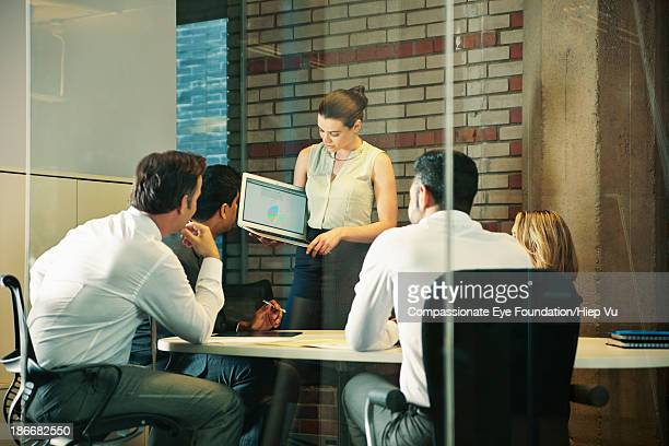 Woman showing laptop presentation to coworkers
