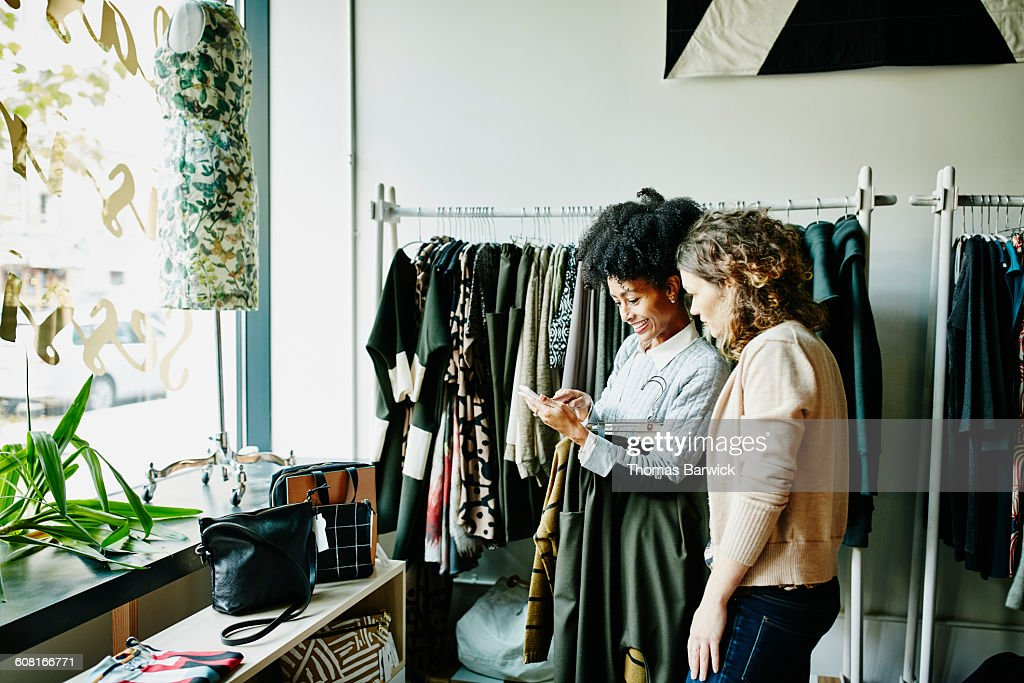 Woman showing shop owner photos on smartphone : Stock Photo