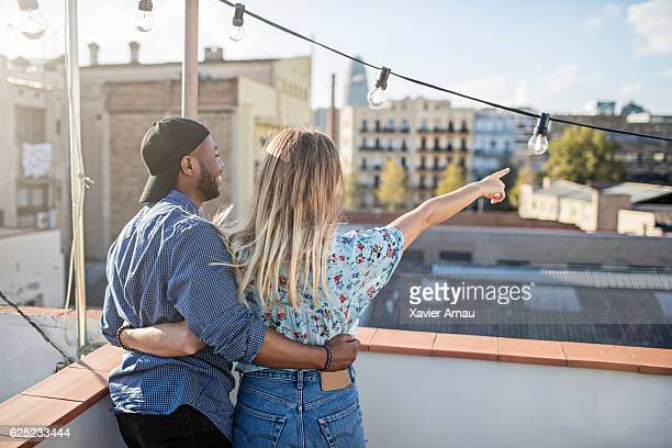 Woman showing something to man on terrace