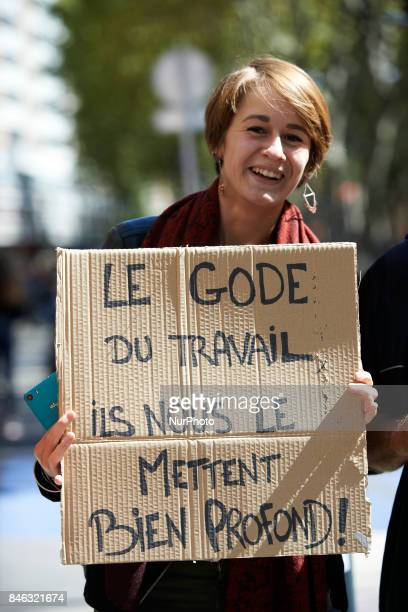 A woman shows a cardborad with a pun in French between 'code' and 'gode' It reads 'The dildo of work they pull it forcefully' More than 10000...