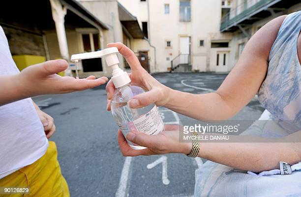 A woman shows a child how to wash his hands with an antibacterial hand gel on August 28 at the Sainte Marie Institute in Caen northwestern France The...