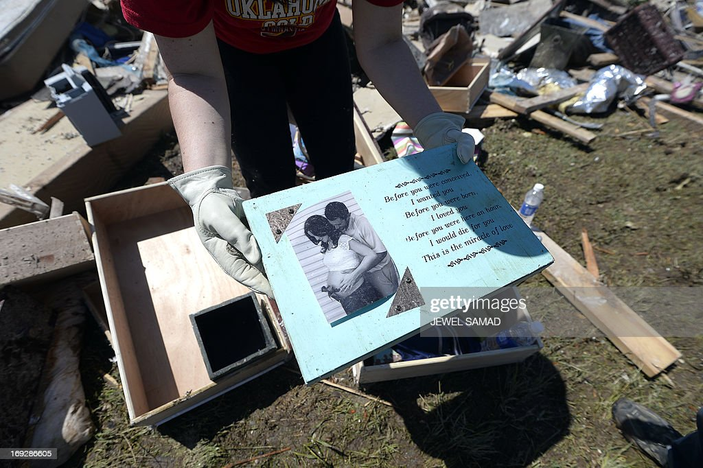 A woman shows a picture she salvaged from her friend's tornado devastated home on May 22, 2013 in Moore, Oklahoma. As rescue efforts in Oklahoma wound down, residents turned to the daunting task of rebuilding a US heartland community shattered by a vast tornado that killed at least 24 people. The epic twister, two miles (three kilometers) across, flattened block after block of homes as it struck mid-afternoon on May 20, hurling cars through the air, downing power lines and setting off localized fires in a 45-minute rampage. AFP PHOTO/Jewel Samad