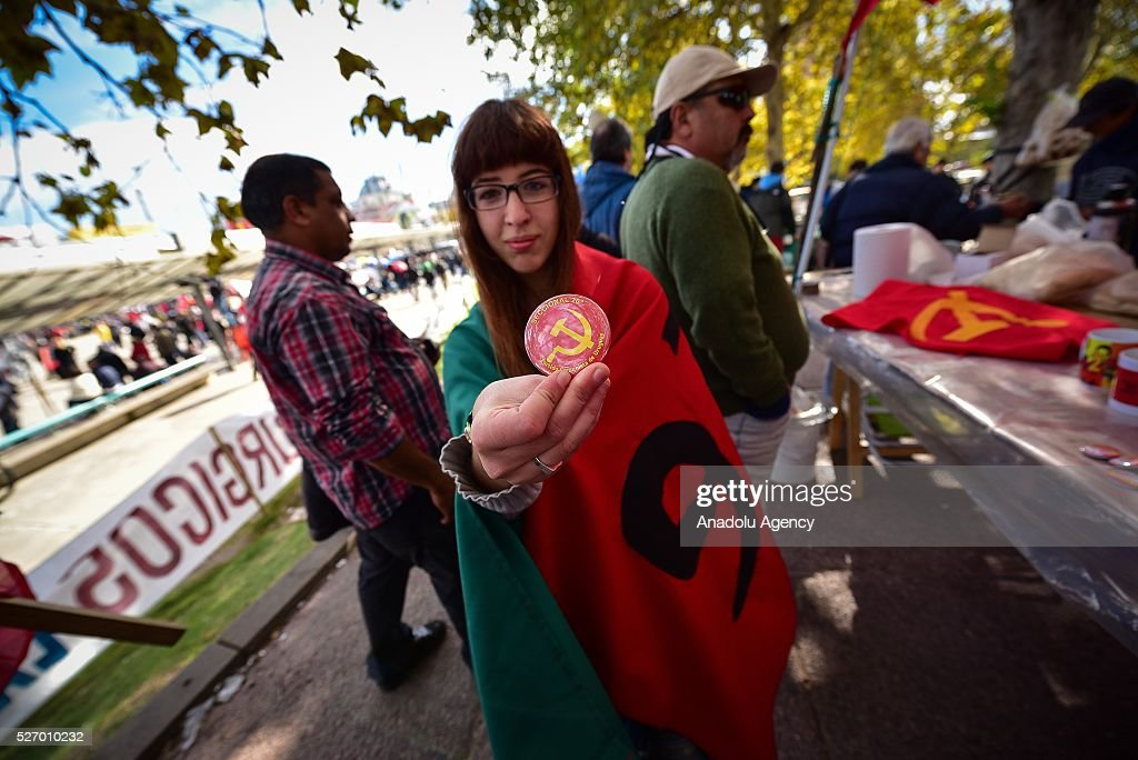 A woman shows a pin of the Communist Party of Uruguay in the act for Labor Day in Montevideo on May 1, 2016.