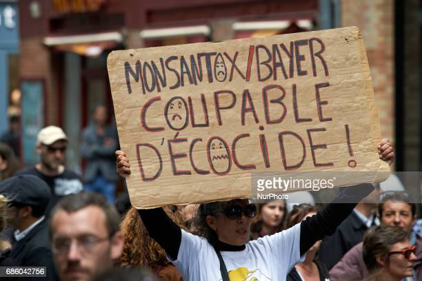 A woman shows a placard reading 'Monsantox/Bayer guilty of ecocide' People march in Toulouse for the International March against Monsanto as...