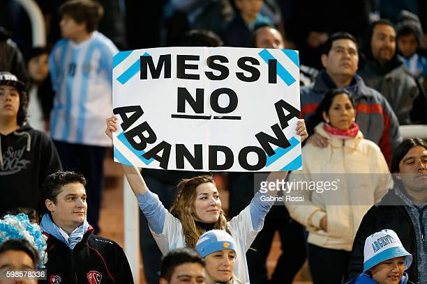 A woman shows a placard that reads in spanish 'Messi Doesn't Abandon' during a match between Argentina and Uruguay as part of FIFA 2018 World Cup...