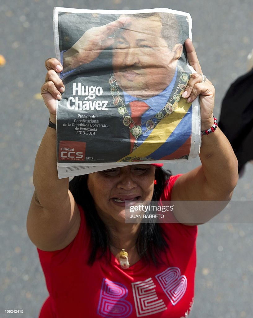 A woman shows a portrait of Venezuelan President Hugo Chavez outside Miraflores presidential palace during an event in homage of Chavez, in Caracas on January 10, 2013. With Chavez ailing and absent, Venezuela's leftist government launches a new presidential term with a display of popular support on the day he was to be inaugurated. The Supreme Court cleared the cancer-stricken president,kwho is recovering from a fourth round of cancer surgery in Havana, to indefinitely postpone his re-inauguration and said his existing administration could remain in office until he is well enough to take the oath. The government has said that he is recovering from complications from surgery, most recently a severe pulmonary infection that had resulted in a 'respiratory insufficiency.' AFP PHOTO/JUAN BARRETO
