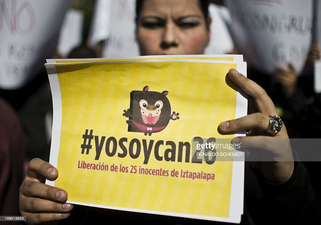 A woman shows a sign reading '#Iamdog26'as she protests after the police caught dozens of stray dogs thought to be involved in the death of four people in Mexico City, on January 11, 2013. Animal rights activists have voiced doubts that dogs are to blame for the death of at least four people in a country torn by runaway crime, but prosecutors insist that only canines could have caused such carnage, with bones exposed and body parts bitten off. Hundreds of Mexico City residents took their dog pets to mobile sterilization units Thursday as the city stepped up a campaign to reduce the number of street dogs after a string of deadly attacks. The city prosecutor's office said stray dogs mauled four people to death, and perhaps two more victims, in the past two weeks. AFP PHOTO/RONALDO SCHEMIDT