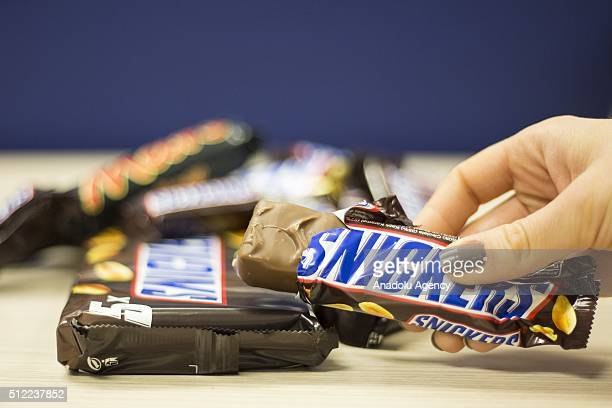 A woman shows a Snickers chocolate bar in her hand in Ankara Turkey on February 25 2016 American candy maker Mars announced Tuesday that it was...