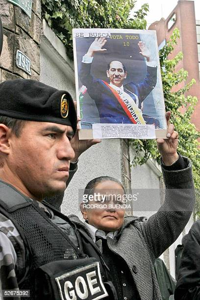 A woman shows a 'wanted' poster of former Ecuadorean President Lucio Gutierrez disfigured in the picture as other former President Abdala Bucaram in...