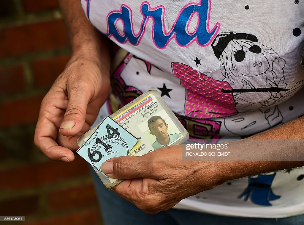 A woman shows an identification card and a ticket to buy at a supermarket as she queues to buy basic food and household items in the poor neighbourhood of Lidice, in Caracas, Venezuela, on May 31, 2016. The oil-dependent nation faces severe food and medicine shortages, school closures and a cut in electricity production which has led to a dramatically shortened workweek for public sector employees. / AFP / RONALDO