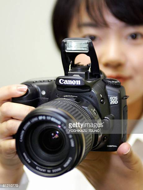 A woman shows Canon's new digital SLR camera 'EOS 20D' with the new 1785mm/F456 vibration reduction zoom lens at the company's headquarters in Tokyo...