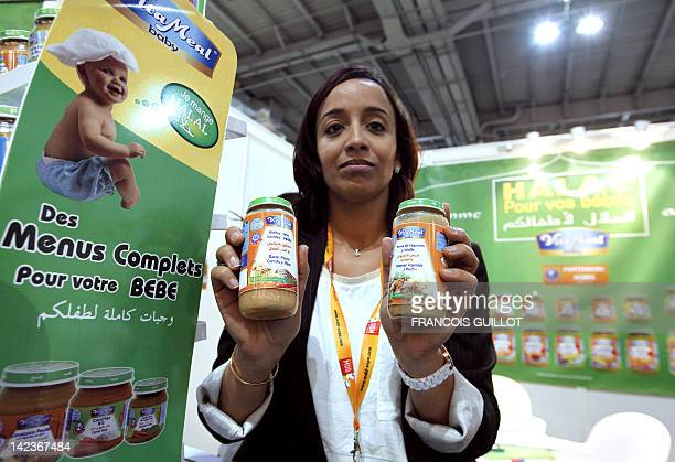 A woman shows halal products for babies at a stand of Halal food products on April 3 2012 during the 9th International Halal and oriental products...