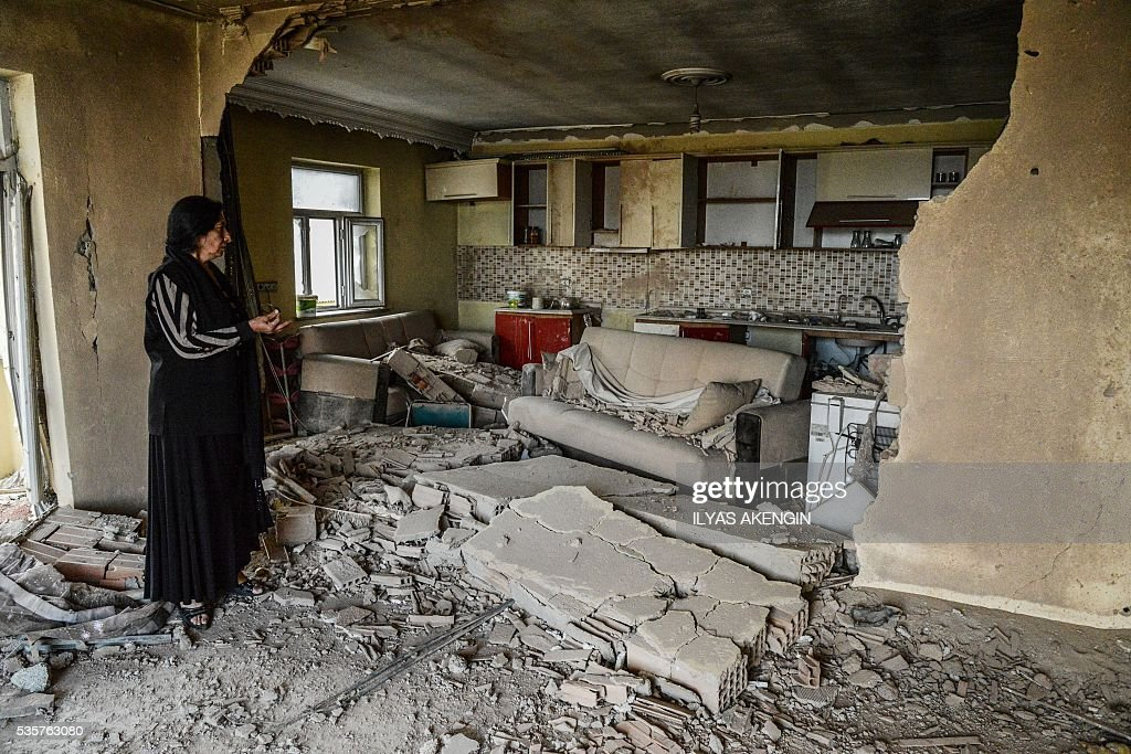 A woman shows her destroyed house to journalists following heavy fightings between government troops and Kurdish fighters after the curfew on May 30, 2016 in the majority Kurdish city town of Yuksekova, southeastern Turkey near the border with Iraq and Iran. / AFP / ILYAS