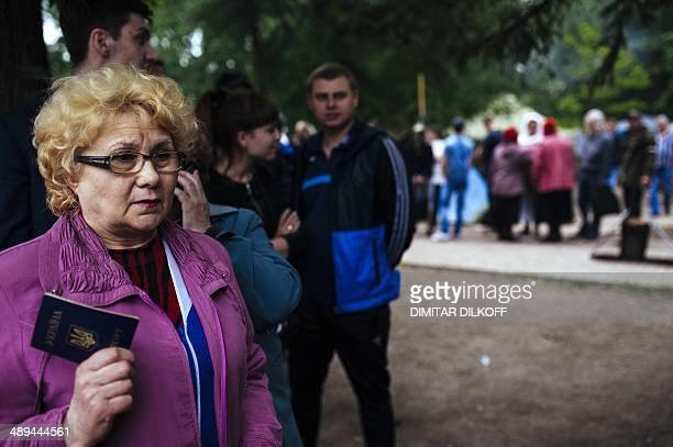 A woman shows her Ukrainian passport as she waits to vote for the referendum called by proRussian rebels in eastern Ukraine to split from the rest of...