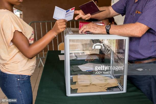 A woman shows her voter card at a polling station on April 22 2017 in Remire Montjoly French Guiana during the first round of the French presidential...