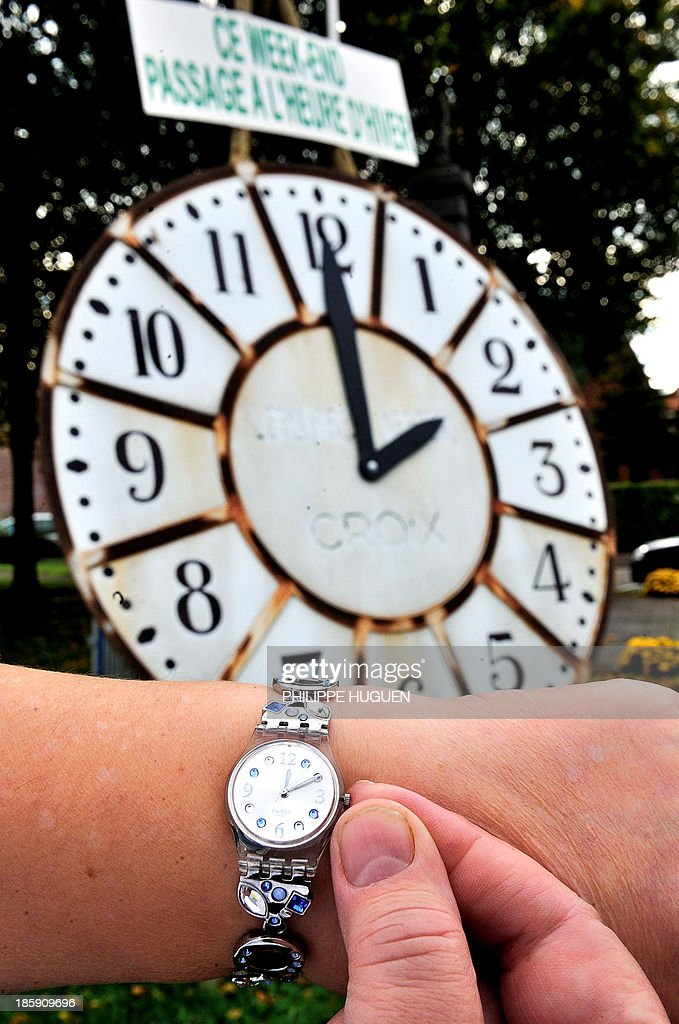 A woman shows her watch on front of a clock with a sign reading 'This week-end switch to the winter time' in Godewaersvelde on October 26, 2013 ahead of the daylight saving time clock change ealry tomorrow.