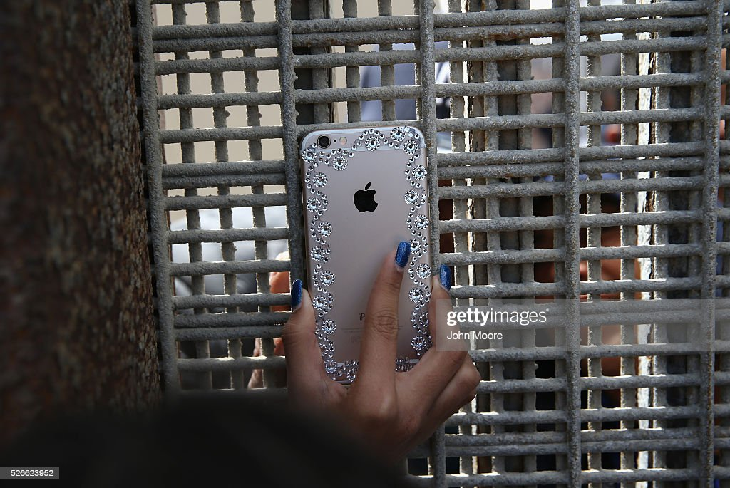 A woman shows loved ones a photo through the U.S.-Mexico Border fence during a 'Opening the Door of Hope' event on April 30, 2016 in San Diego, California. Five families, with some members living in Mexico and others in the United States, were permitted to meet and embrace for three minutes each at a door in the fence, which the U.S. Border Patrol opened to celebrate Mexican Children's Day. It was only the third time the fence, which separates San Diego from Tijuana, had been opened for families to briefly reunite. The event was planned by the immigrant advocacy group Border Angels.