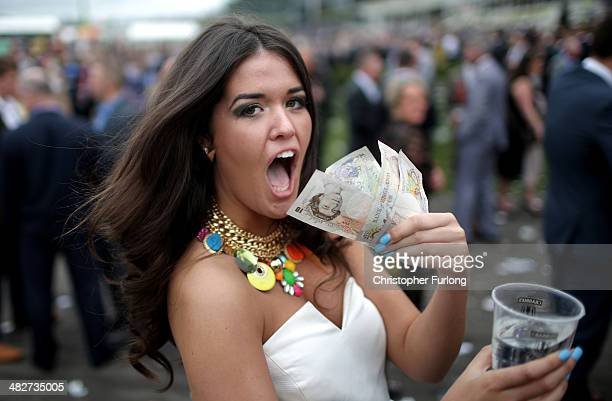 A woman shows off her winnings as racegoers enjoy the party atmosphere of Ladies Day at the Aintree Grand National Festival meeting on April 4 2014...