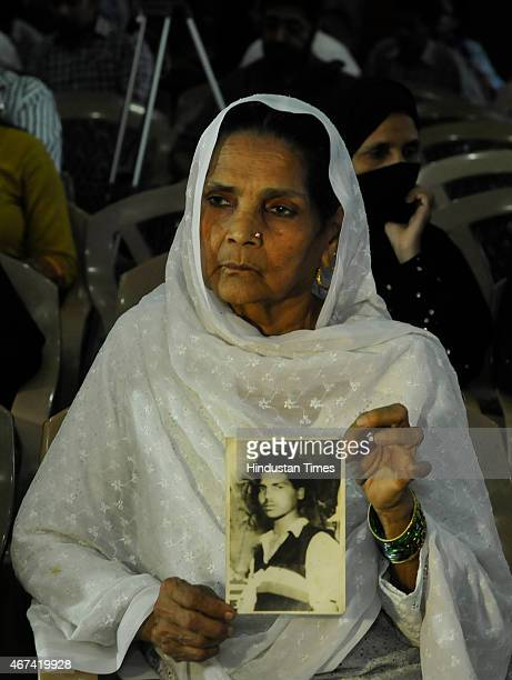 A woman shows picture of her relative who was killed in 1987 Hashimpura massacre during a press conference to express their disappointment at the...