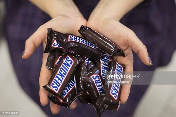 A woman shows Snickers chocolate bars in her hand in Ankara Turkey on February 25 2016 American candy maker Mars announced Tuesday that it was...
