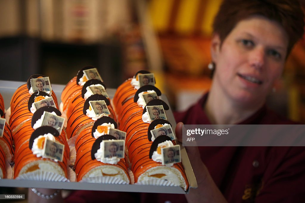 A woman shows special cakes with a picture of Queen Beatrix in a bakery in Leeuwarden, The Netherlands, on January 29, 2013. The Queen announced yesterday her abdication. AFP PHOTO/ CATRINUS VAN DER VEEN netherlands out