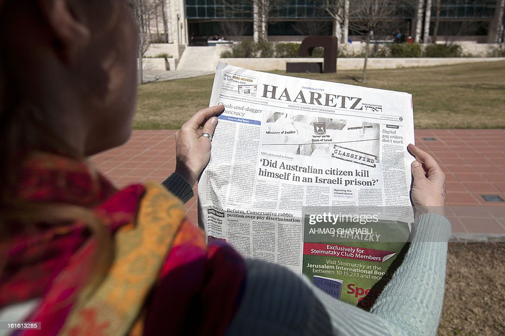 A woman shows the latest issue of the Haaretz daily newspaper whose cover page raises a question on the alleged suicide of an Australian prisoner with ties to Mossad on February 13, 2013 in Jerusalem. Twenty-four hours after the emergence of an explosive investigative report by Australia's ABC news, the Israeli censor moved to ease the total blackout on coverage of the incident, allowing the local press to publish details from the report.