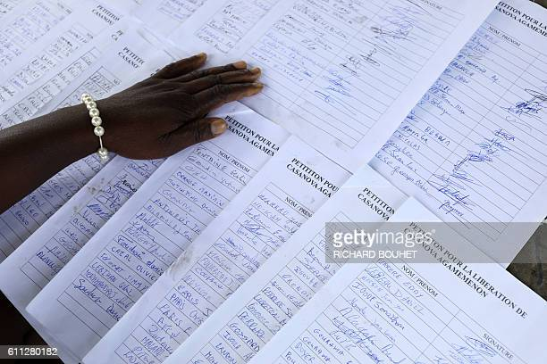 A woman shows the pages of a signed petition calling for the release on parole of Casanova Agamemnon one of the oldest prisoners of France in...