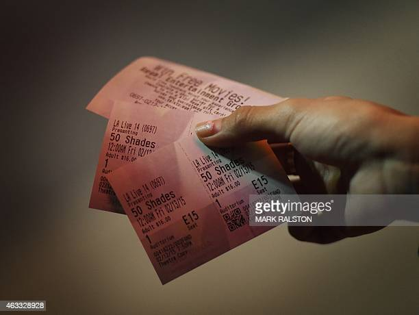 A woman shows tickets to the media before the film 'Fifty Shades of Grey' on its opening day in Los Angeles on February 12 2015 'Fifty Shades of...