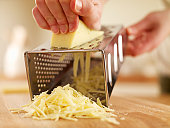 Woman shredded cheese with grater