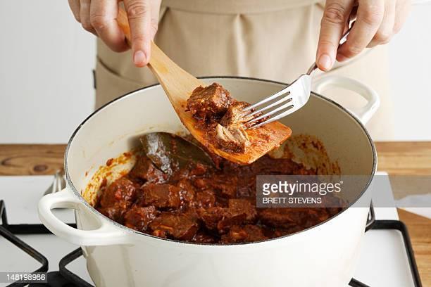 Woman shredding meat in pot