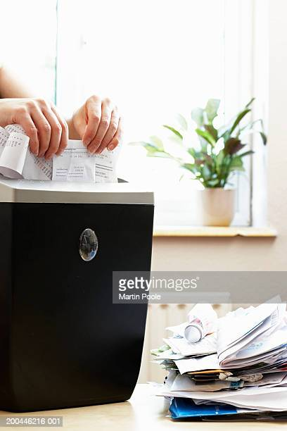 Woman shredding receipts in paper shredder, close-up