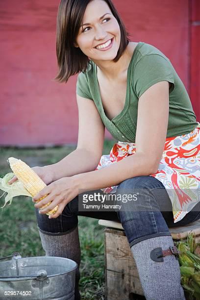Woman shucking corn