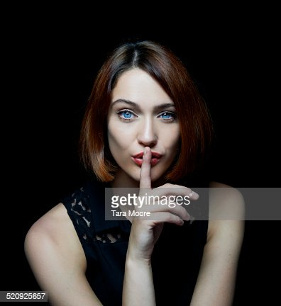 woman shushing with finger up to mouth