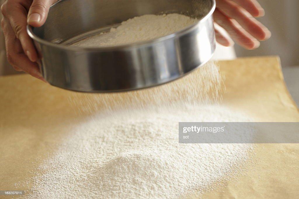 Woman sieving flour,close up : Stock Photo
